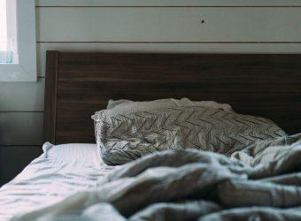 Drevená posteľ s vankúšom a odhrnutou perinou na pravú stranu