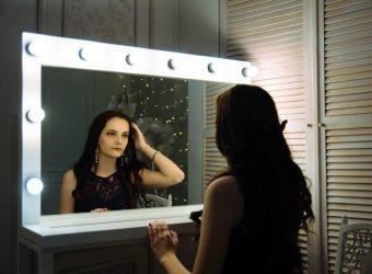 Slečna bruneta sa pozerá do zrkadla, ktoré je je osvetlené na okrajoch rámov so žiarovkami.