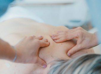 Ruky, ktoré masírujú ženský chrbát