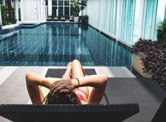 Slečna v bikinách sediaca pred krytím bazénom, sprava z okien presvitlá slnko